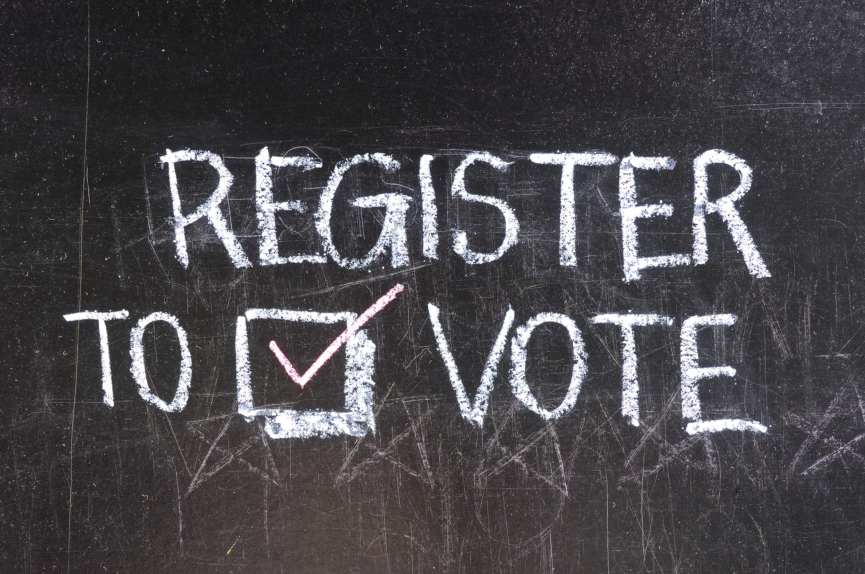 chalk words on blackboard says register to vote.  Click on it to sign up for our newsletter.