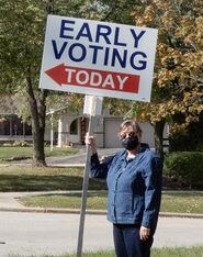 woman with mask holding sign that says early voting. its a fall day