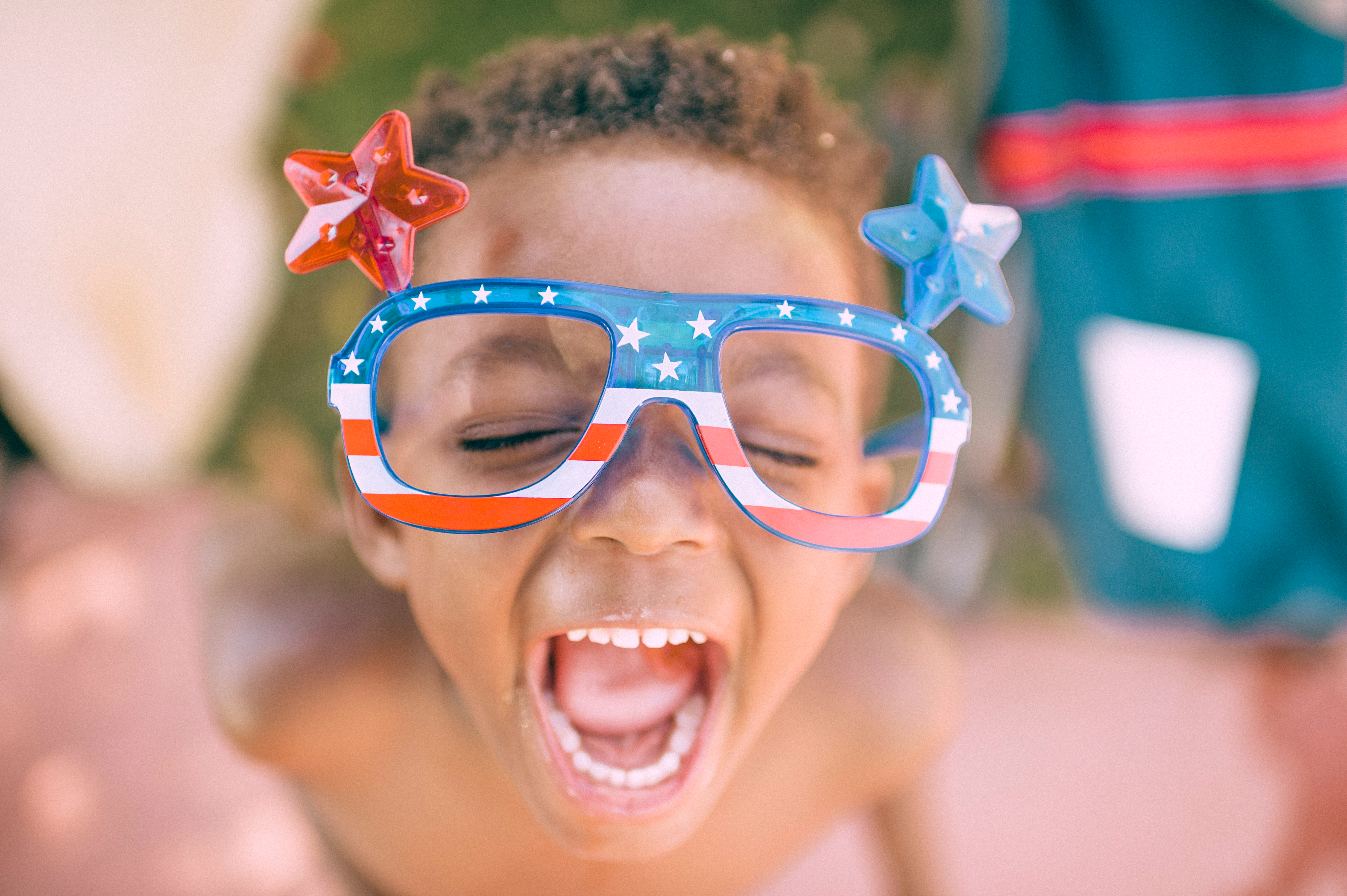 child with red white and blue, stars and stripes glasses